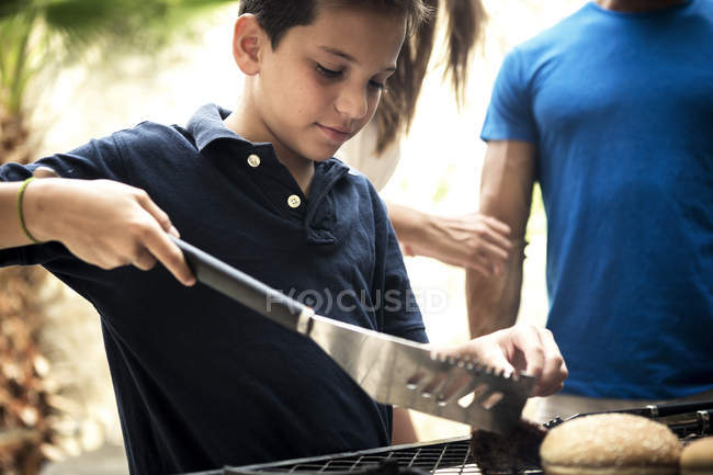 Boy turning food on barbecue. — Stock Photo