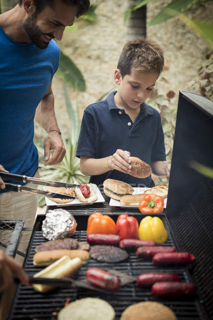 Man and boy standing at barbecue — Stock Photo