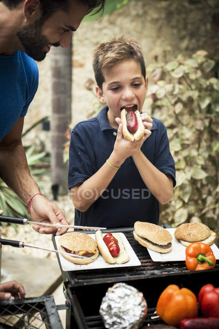 Boy and man standing at open barbecue — Stock Photo