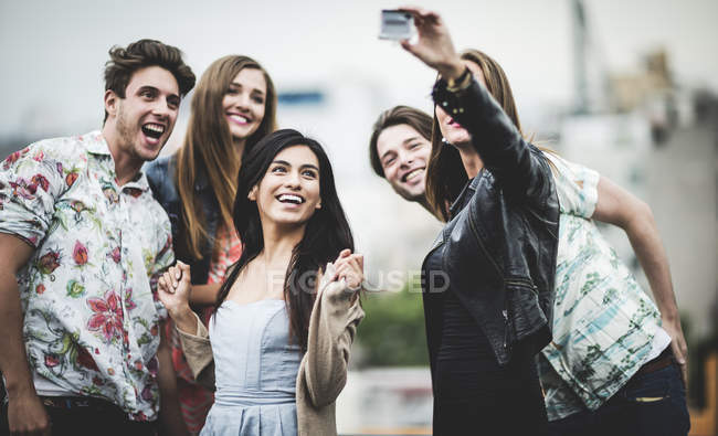 Five young people standing on rooftop — Stock Photo