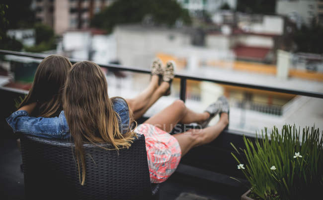 Junge Frauen sitzen auf Dach — Stockfoto