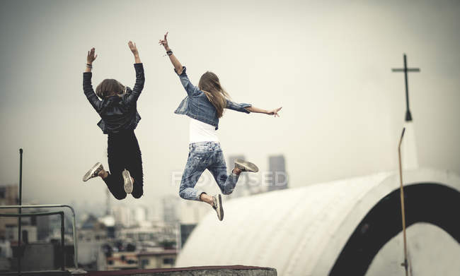 Women jumping on rooftop — Stock Photo
