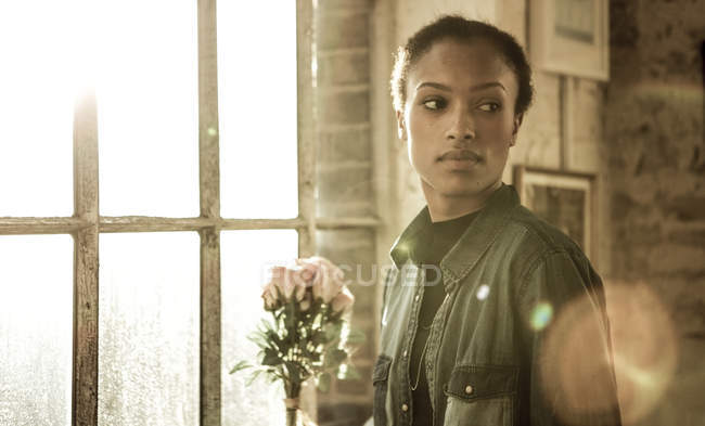 Young woman standing by window — Stock Photo