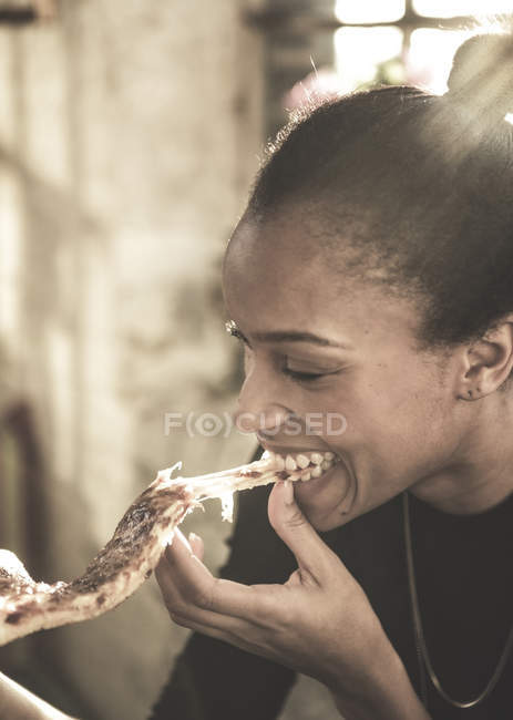 Woman eating slice of pizza. — Stock Photo