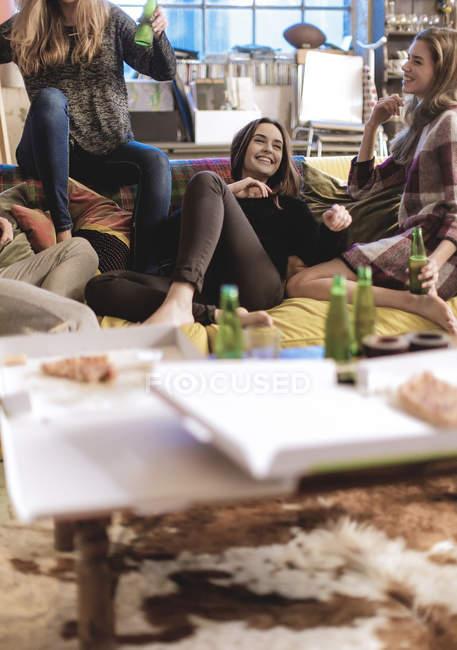 Женщины, сидящие на диване, смеющиеся — стоковое фото