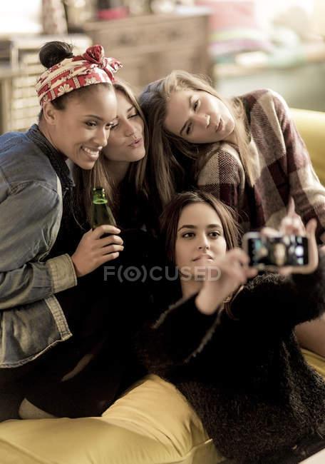 Молодые женщины сидят на диване, улыбаясь — стоковое фото