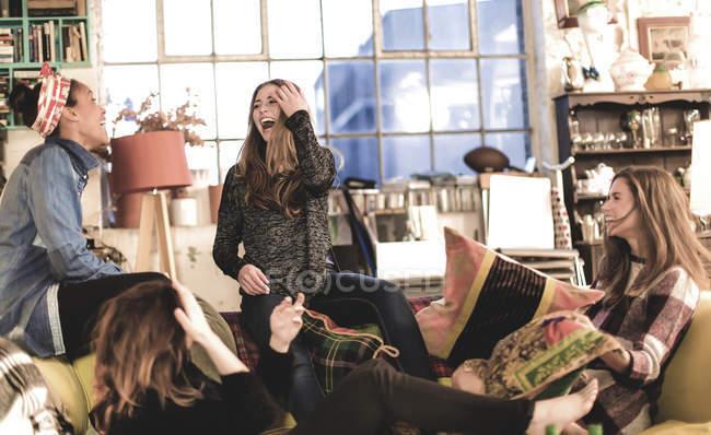 Женщины сидят в помещении на диване и смеются — стоковое фото