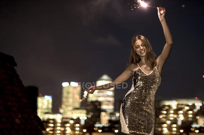 Young woman holding sparkler — Stock Photo