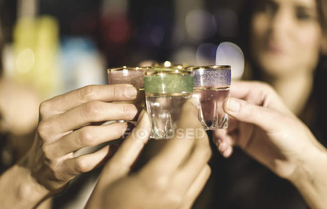 Group at party holding shot glasses — Stock Photo