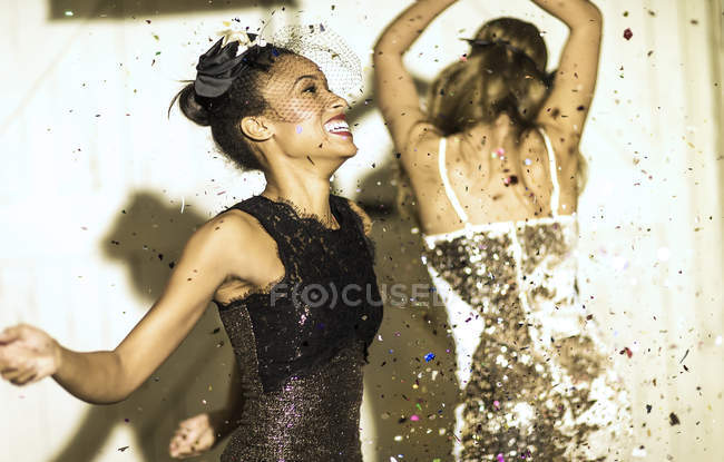 Young women dancing with confetti falling. — Stock Photo