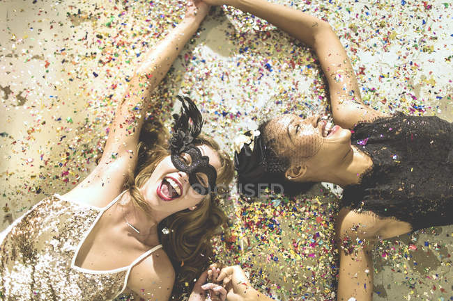 Young women lying on carpet in confetti — Stock Photo