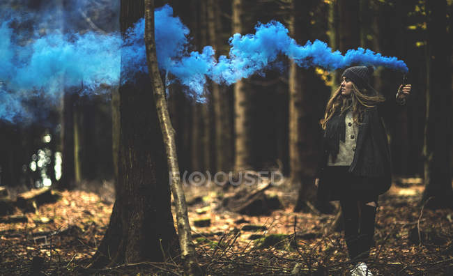 Woman holding blue smoke flare in forest. — Stock Photo