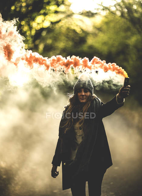 Woman holding orange smoke flare in forest. — Stock Photo