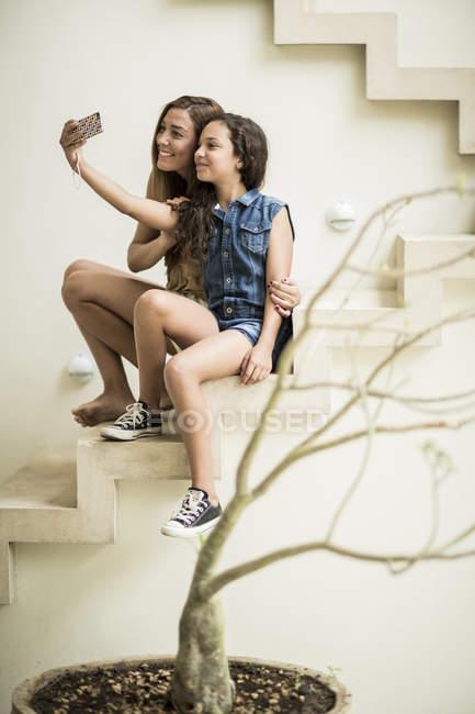 Женщина и девушка сидит на открытый шаги — стоковое фото