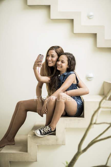 Жінка і дівчина сидить на відкритому повітрі кроки — Stock Photo