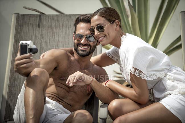 Couple sitting on sun loungers — Stock Photo