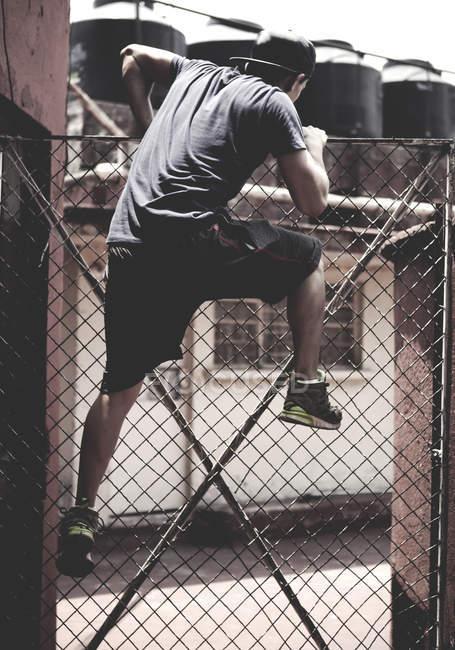 Человек перелезает через забор — стоковое фото