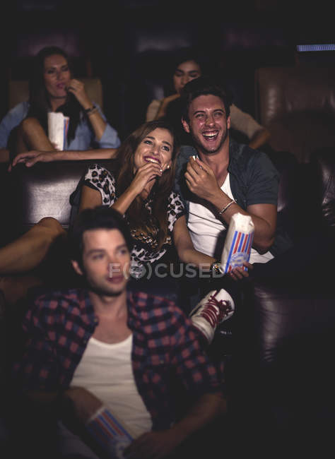 Group of young people sitting in cinema — Stock Photo