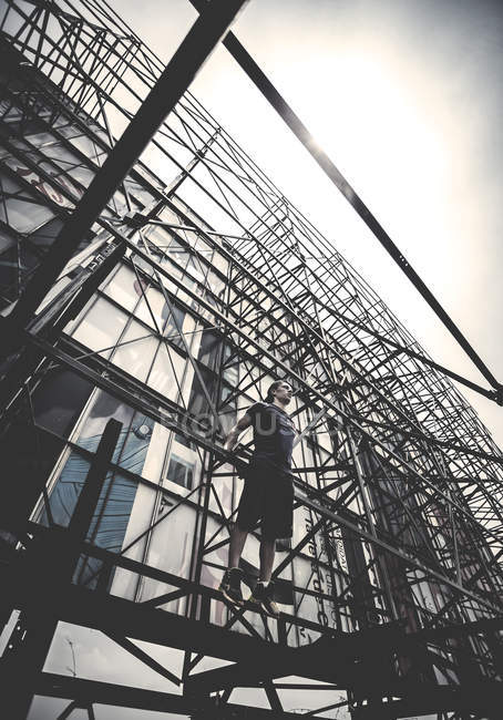Young man standing on scaffolding — Stock Photo
