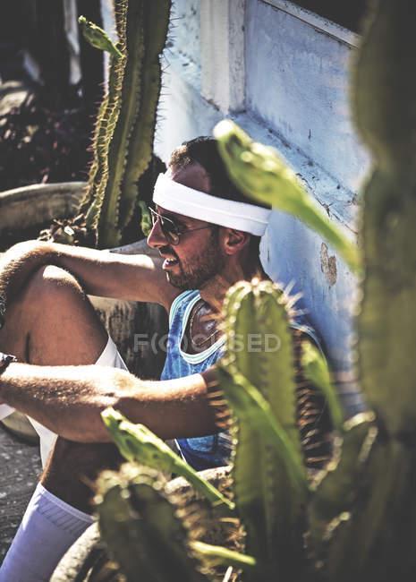 Man sitting between cacti growing in pots. — Stock Photo