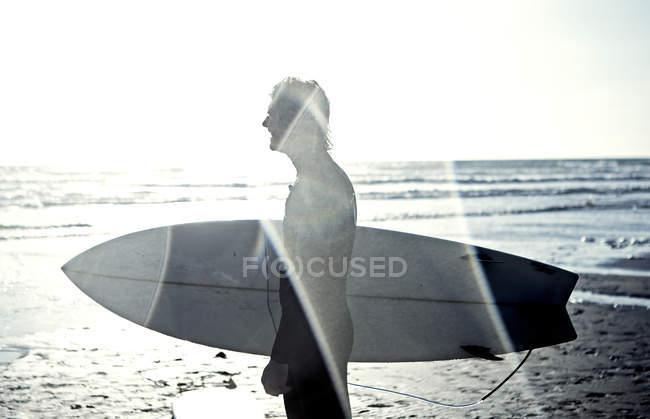 Uomo in muta che trasporta tavola da surf . — Foto stock