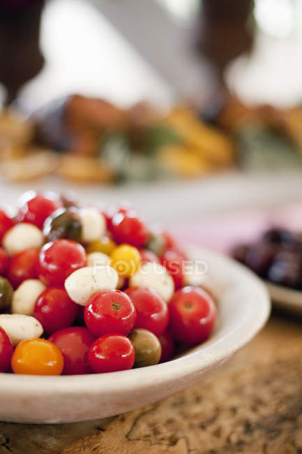 Red and orange tomatoes in bocconcini salad — Stock Photo