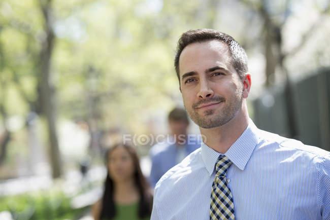 Homem de terno a desviar o olhar na rua com pessoas sem foco em plano de fundo — Fotografia de Stock
