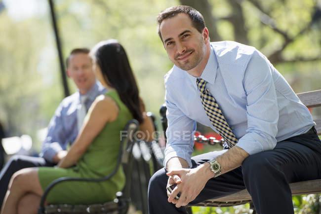 Мужчина в костюме глядя в камеру сидя на скамейках в парке с коллегами — стоковое фото