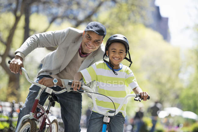 African american father and son bicycling and having fun in park — Stock Photo