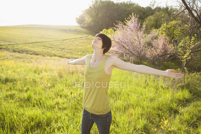 Woman with arms outstretched standing in grassy field in spring. — Stock Photo