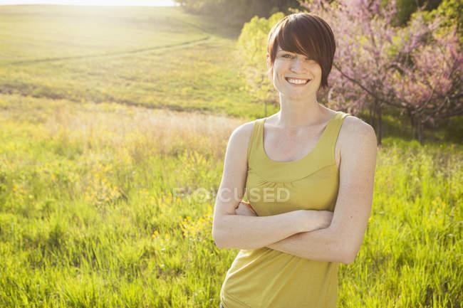 Жінка з стоячи в трав'янистих області навесні, склавши руки. — стокове фото
