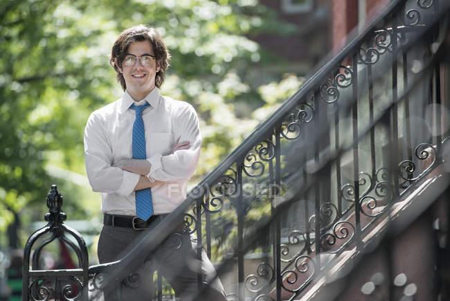 Человек в белой рубашке и синий галстук, стоя с сложив вне таунхаус — стоковое фото