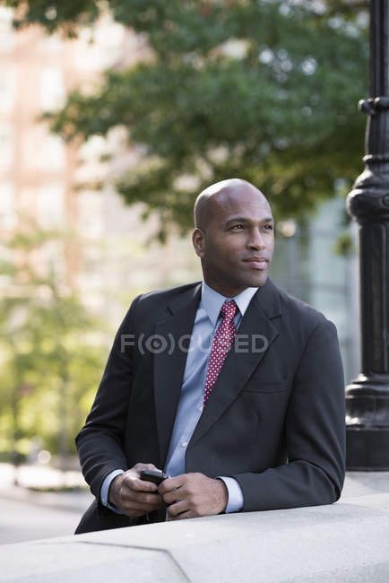 Man in suit leaning on balustrade under a lamppost — Stock Photo
