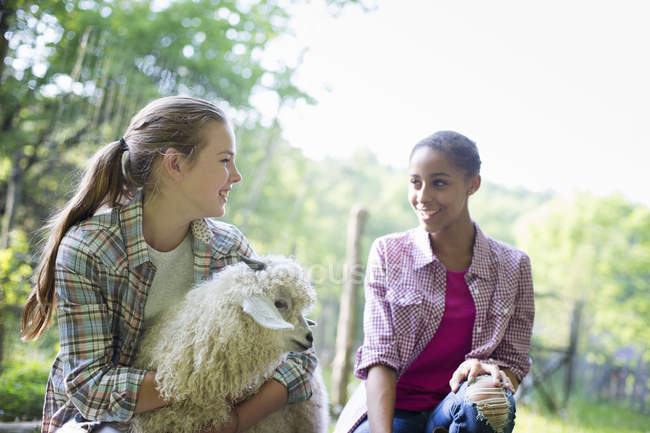 Two young women on farm with very fluffy angora goat. — Stock Photo