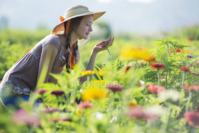 Side view of teenage girl smelling flowers in field — Stock Photo