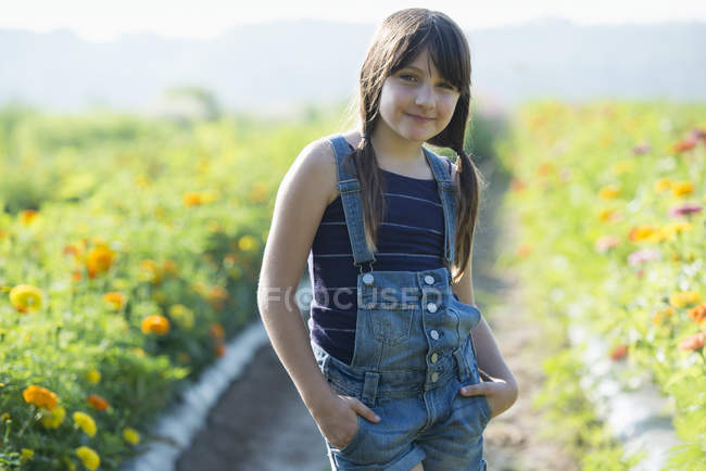 Teenage girl standing in flower field — Stock Photo