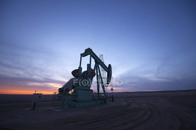 Pumpjack at oil drilling site — Stock Photo
