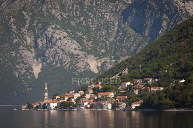Aldeia e lago nas encostas da montanha — Fotografia de Stock