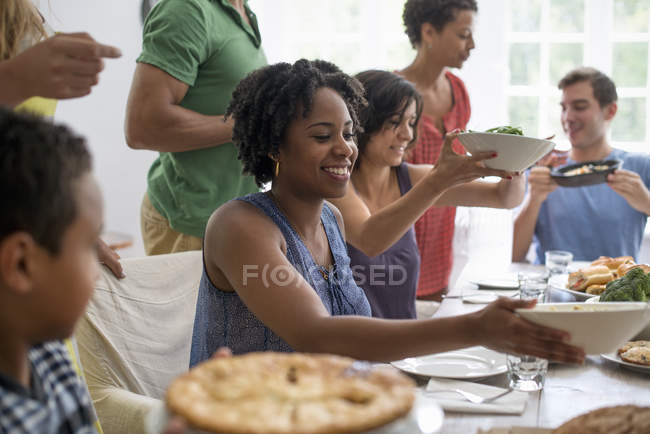 Family of men, women and boy sharing meal at dining table. — Stock Photo