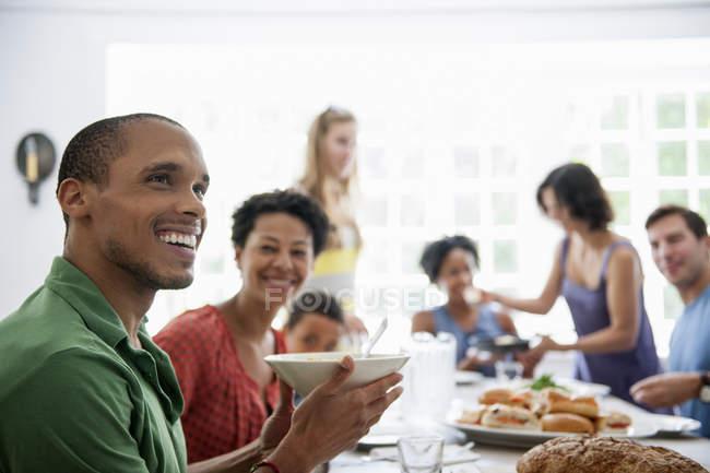 Familie aus Männern, Frauen und Kindern beim gemeinsamen Essen am Esstisch. — Stockfoto