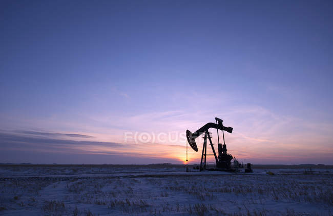 Oil drilling rig and pumpjack on flat plain in Canadian oil field at sunset. — Stock Photo