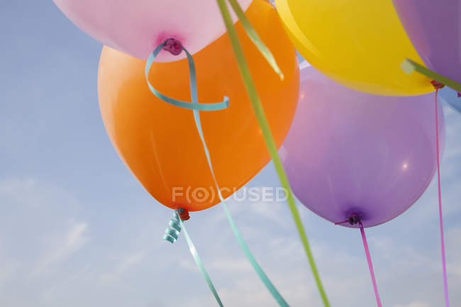Bunch of colorful balloons floating in air against blue sky. — Stock Photo