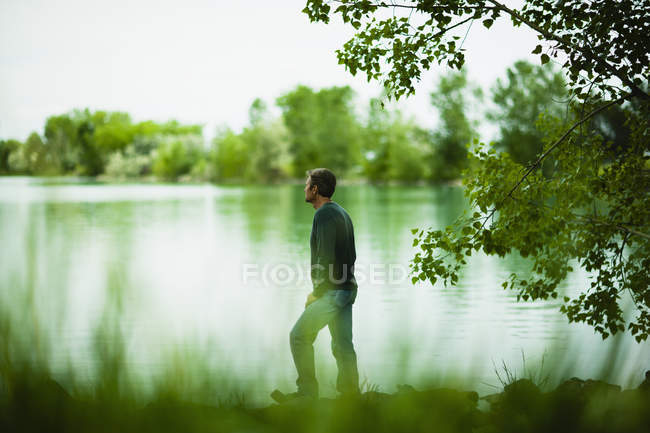 Человек стоял и глядя на вид через озеро воды. — стоковое фото