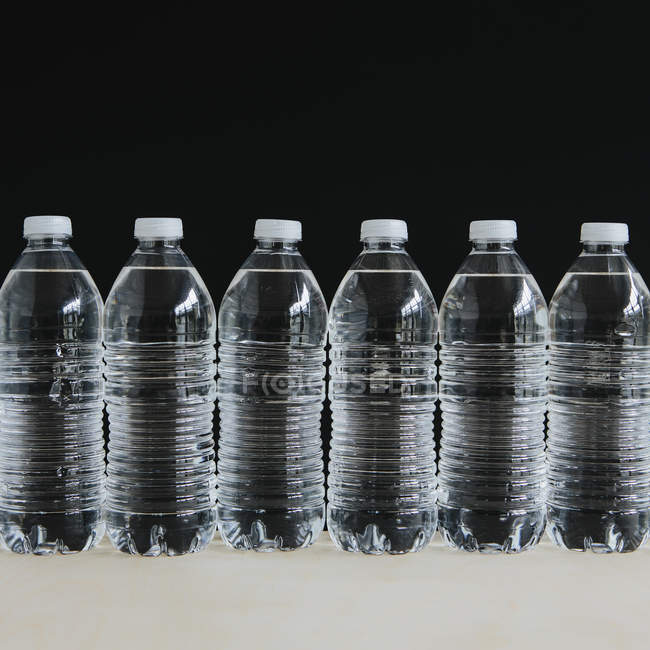 Row of clear plastic water bottles filled with filtered water. — Stock Photo