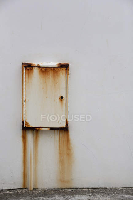 Wall-mounted metal box with rust stains. — Stock Photo