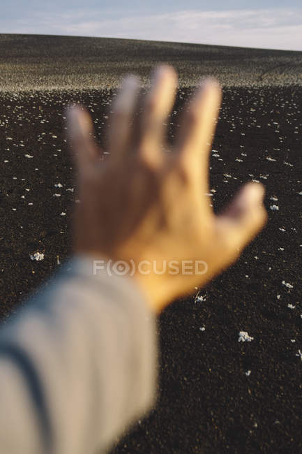 Male hand in foreground of solidified lava field. — Stock Photo