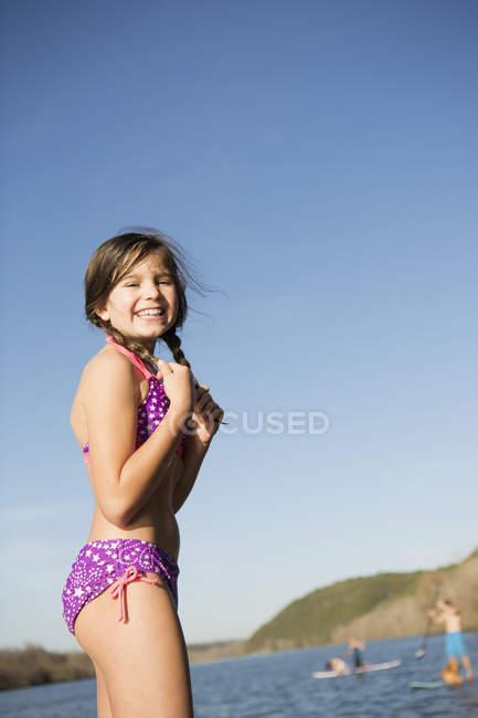 Pré adolescente sur la jetée avec paddleboarders en arrière-plan — Photo de stock