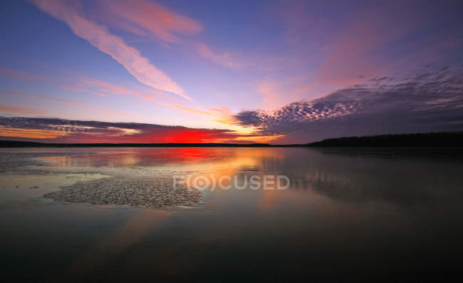 Sky and cloud pattern reflecting in frozen surface of lake. — Stock Photo