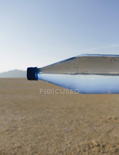 Bottle of water in landscape of Black Rock Desert in Nevada — Stock Photo