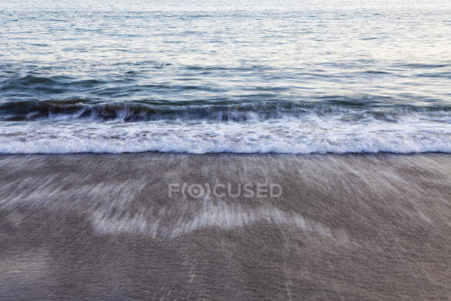 Waves breaking on shore at dusk. — Stock Photo